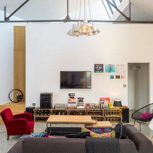 Inspiration pour une salle de séjour design de taille moyenne et ouverte avec un mur blanc, béton au sol et un téléviseur fixé au mur.