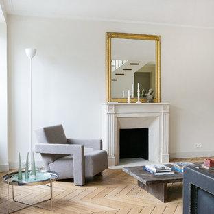 Exemple d'une salle de séjour tendance de taille moyenne et ouverte avec un mur blanc, un sol en bois clair, une cheminée standard, un manteau de cheminée en pierre et aucun téléviseur.