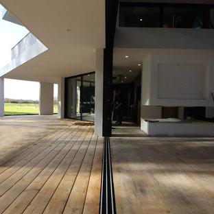 トゥールーズの大きいコンテンポラリースタイルのおしゃれなファミリールーム (白い壁、セラミックタイルの床、吊り下げ式暖炉、レンガの暖炉まわり、茶色い床) の写真