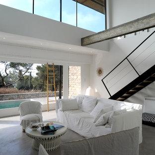 Idées déco pour une salle de séjour contemporaine de taille moyenne avec un mur blanc et béton au sol.