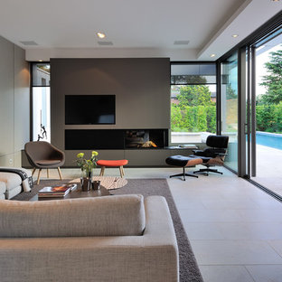 Inspiration for a huge contemporary open concept family room remodel in Lyon with a ribbon fireplace, a metal fireplace, gray walls and a wall-mounted tv