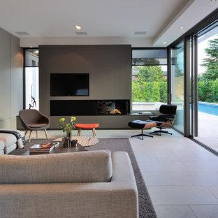 Exemple d'une très grande salle de séjour tendance ouverte avec une cheminée ribbon, un manteau de cheminée en métal, un mur gris et un téléviseur fixé au mur.