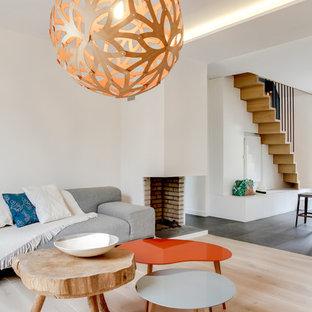 Cette photo montre une salle de séjour tendance ouverte et de taille moyenne avec un mur blanc, un sol en bois clair, une cheminée d'angle et aucun téléviseur.