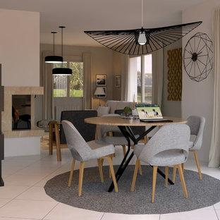 ナントの中くらいのコンテンポラリースタイルのおしゃれなオープンリビング (白い壁、セラミックタイルの床、コーナー設置型暖炉、石材の暖炉まわり、据え置き型テレビ、白い床) の写真