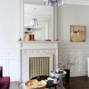Inspiration pour une salle de séjour design de taille moyenne et ouverte avec un mur gris, un sol en bois foncé, une cheminée standard, un manteau de cheminée en pierre et aucun téléviseur.