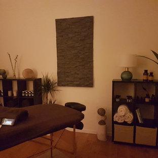 Immagine di una palestra in casa tropicale di medie dimensioni con pareti bianche, parquet chiaro e pavimento beige