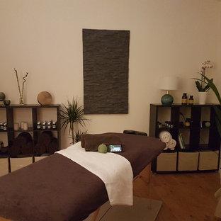 Esempio di una palestra in casa tropicale di medie dimensioni con pareti bianche, parquet chiaro e pavimento beige