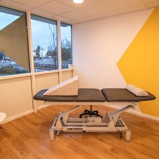 Cette photo montre une grand salle de musculation scandinave avec un mur blanc, un sol en vinyl et un sol beige.