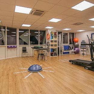 Exemple d'une grand salle de musculation scandinave avec un mur blanc, un sol en vinyl et un sol beige.