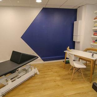 Idée de décoration pour une grand salle de musculation nordique avec un mur blanc, un sol en vinyl et un sol marron.
