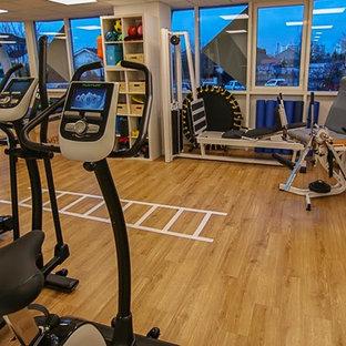 Réalisation d'une grand salle de musculation nordique avec un mur blanc, un sol en vinyl et un sol marron.