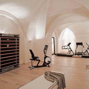 Immagine di una grande palestra multiuso con pareti bianche, pavimento in laminato e pavimento beige