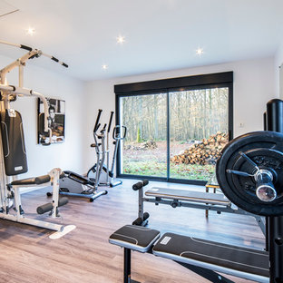 Home weight room - mid-sized modern light wood floor home weight room idea in Le Havre with white walls