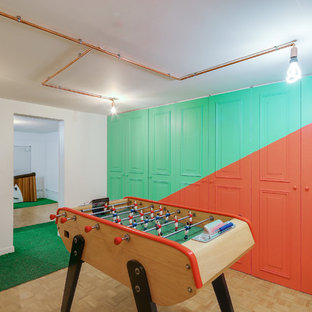 Example of a small minimalist medium tone wood floor and green floor multiuse home gym design in Paris with red walls
