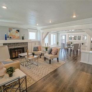Idee per un grande soggiorno minimal aperto con sala formale, pareti bianche, pavimento in laminato, stufa a legna, cornice del camino in mattoni, nessuna TV e pavimento marrone