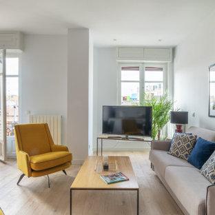 Imagen de salón abierto, contemporáneo, pequeño, con paredes blancas, suelo de madera clara, suelo beige y televisor en una esquina