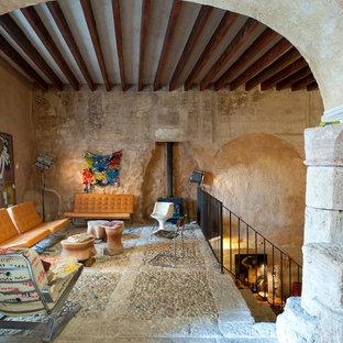 Ejemplo de salón tipo loft, mediterráneo, de tamaño medio, sin televisor, con suelo beige, paredes beige, estufa de leña y marco de chimenea de metal