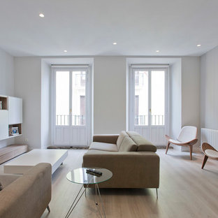 Modelo de salón abierto, minimalista, de tamaño medio, con suelo de madera clara