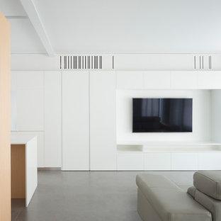 Ejemplo de salón abierto, moderno, con paredes blancas, televisor colgado en la pared y suelo gris