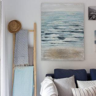 他の地域の中サイズのビーチスタイルのおしゃれなLDK (フォーマル、白い壁、磁器タイルの床、壁掛け型テレビ、グレーの床) の写真