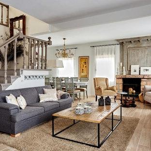 Imagen de salón abierto, campestre, grande, con paredes blancas, chimenea tradicional, marco de chimenea de piedra y suelo beige