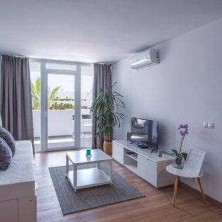 Ejemplo de salón para visitas costero con paredes blancas, suelo de madera en tonos medios, televisor independiente y suelo beige