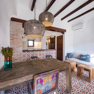 Diseño de salón abierto, mediterráneo, pequeño, sin chimenea y televisor, con paredes blancas, suelo de baldosas de cerámica y suelo rojo