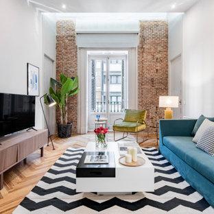 Inredning av ett modernt mellanstort vardagsrum, med vita väggar, mellanmörkt trägolv, en fristående TV och brunt golv