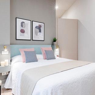 Modelo de salón actual, de tamaño medio, con paredes blancas, suelo de madera clara y suelo beige