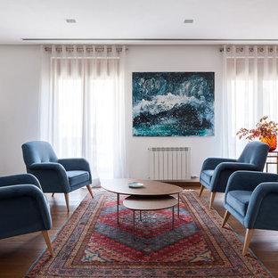 Ejemplo de salón abierto, actual, grande, con paredes blancas, suelo de madera en tonos medios, chimenea tradicional y suelo marrón