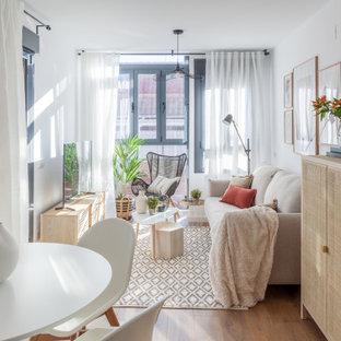 Kleines, Offenes Skandinavisches Wohnzimmer mit weißer Wandfarbe, dunklem Holzboden, freistehendem TV und braunem Boden in Madrid