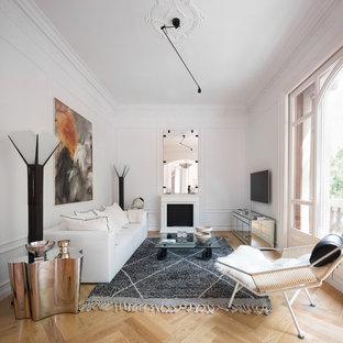 Imagen de salón para visitas escandinavo con paredes blancas, suelo de madera clara, chimenea tradicional, televisor colgado en la pared y suelo beige