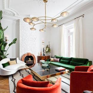 Imagen de salón para visitas actual, sin televisor, con paredes blancas, suelo de madera en tonos medios y chimenea tradicional