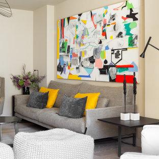 Diseño de salón contemporáneo con paredes beige, suelo de madera en tonos medios y suelo marrón