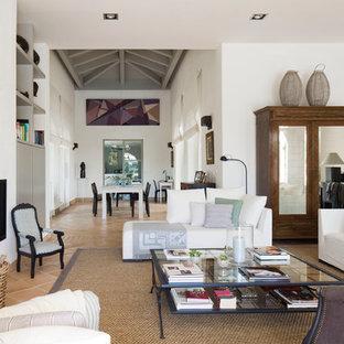 Modern inredning av ett stort allrum med öppen planlösning, med ett finrum, vita väggar, klinkergolv i terrakotta och en öppen vedspis