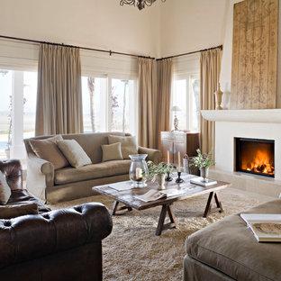 マドリードの広い地中海スタイルのおしゃれな独立型リビング (フォーマル、ベージュの壁、標準型暖炉、カーペット敷き、漆喰の暖炉まわり、テレビなし) の写真