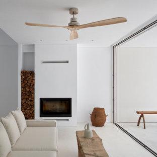 Imagen de salón abierto, moderno, con paredes blancas, suelo de cemento, chimenea tradicional y suelo blanco