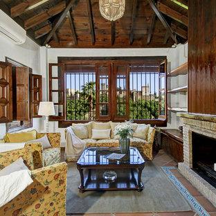 Modelo de salón para visitas mediterráneo, sin televisor, con paredes blancas, suelo de baldosas de terracota, chimenea tradicional y marco de chimenea de ladrillo