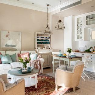 Imagen de salón abierto, romántico, de tamaño medio, sin chimenea y televisor, con paredes beige y suelo de madera clara