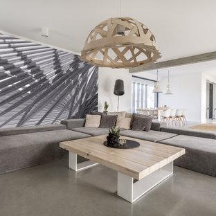 Modelo de salón abierto, moderno, con paredes blancas, suelo de cemento y suelo gris