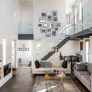 Modelo de salón abierto, contemporáneo, con paredes blancas, suelo gris, chimenea tradicional y televisor colgado en la pared