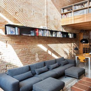 バルセロナの広いインダストリアルスタイルのおしゃれなLDK (赤い壁、コンクリートの床、青い床、三角天井、レンガ壁) の写真