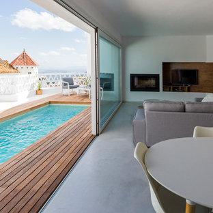 他の地域の中サイズの地中海スタイルのおしゃれなLDK (フォーマル、白い壁、コンクリートの床、薪ストーブ、埋込式メディアウォール) の写真