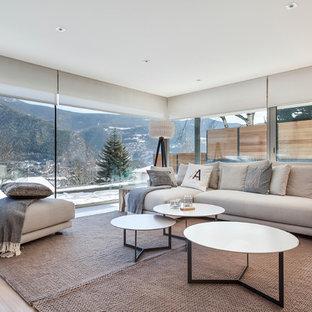Modelo de salón para visitas abierto, escandinavo, grande, sin chimenea y televisor, con suelo de madera clara y paredes blancas