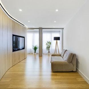 Modelo de salón contemporáneo con paredes blancas, suelo de madera clara, pared multimedia y suelo beige