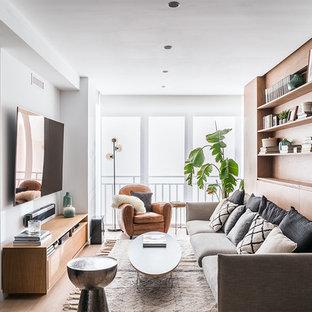Modelo de salón contemporáneo con suelo de madera en tonos medios, paredes blancas, televisor colgado en la pared y suelo marrón