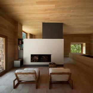 Modelo de salón para visitas abierto, actual, grande, sin televisor, con suelo de baldosas de terracota, chimenea lineal y paredes marrones