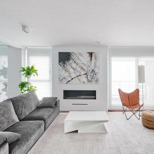 Diseño de salón contemporáneo con paredes blancas, suelo de madera en tonos medios, chimenea lineal y marco de chimenea de yeso