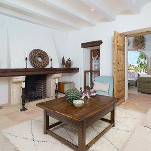 Modelo de salón para visitas cerrado, mediterráneo, sin televisor, con paredes blancas, chimenea tradicional, marco de chimenea de piedra, suelo de baldosas de terracota y suelo beige