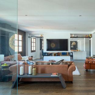 Imagen de salón abierto, contemporáneo, grande, con paredes blancas, suelo de madera en tonos medios, chimenea de doble cara, marco de chimenea de yeso, televisor colgado en la pared y suelo marrón
